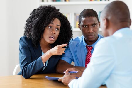 Angry african american couple rejecting offer of real estate agent