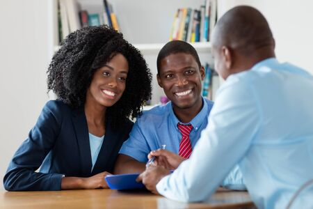 Agente inmobiliario ofrece nueva casa para pareja afroamericana Foto de archivo