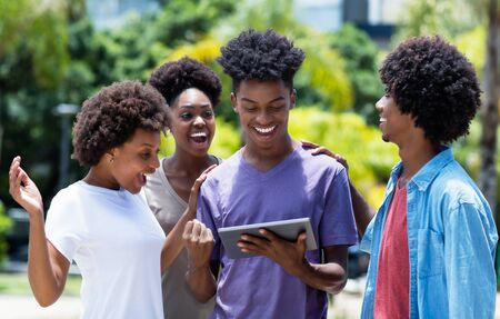 Laughing group of african american university students with digital tablet