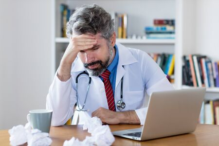 Mature male general practitioner with problems Stock Photo