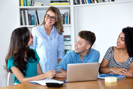 Beautiful female teacher learning with group of multi ethnic college students Stock Photo