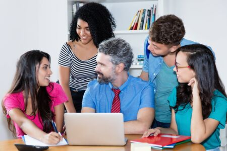 Mature male teacher with group of multi ethnic college students Stock Photo