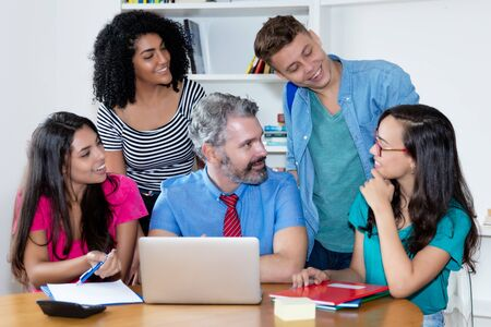 Mature male teacher talking with group of multi ethnic college students Stock Photo