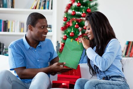 Laughing african american love couple with gifts and christmas presents