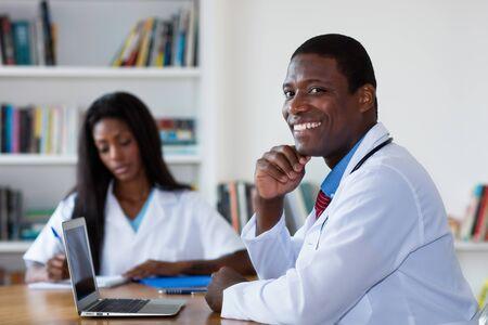Médico afroamericano en la computadora con la enfermera