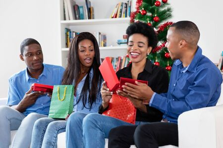 Laughing african african family celebrating christmas with gifts and presents