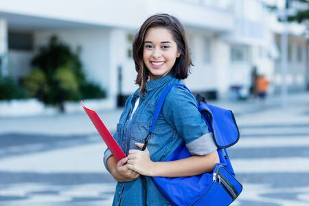 Laughing spanish female student with backpack