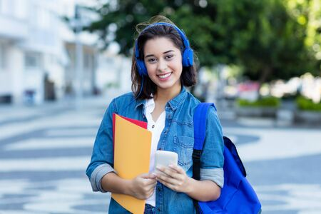 Beautiful spanish female student with backpack and earphones Stockfoto