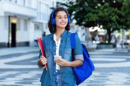 Pretty spanish female student with backpack and earphones