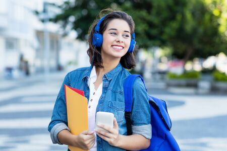 Cute spanish female student with backpack and earphones