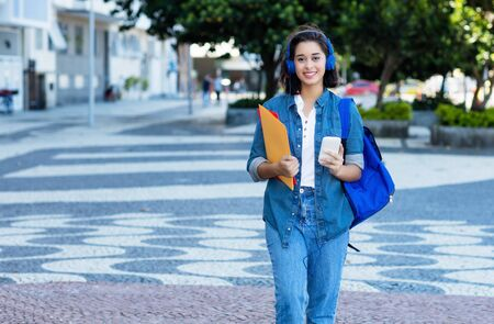 Young spanish female student with backpack and earphones Stockfoto