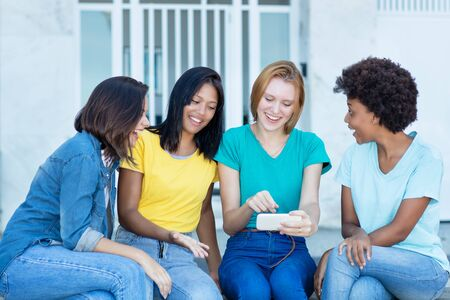 Group of latin and hispanic and african american female young adults watching movie clip at phone