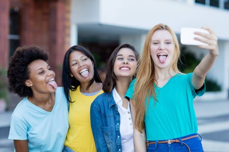 Group of multi ethnic young adult woman taking crazy selfie Reklamní fotografie