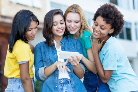 Group of latin and hispanic and african american girls watching movie clip at cellphone