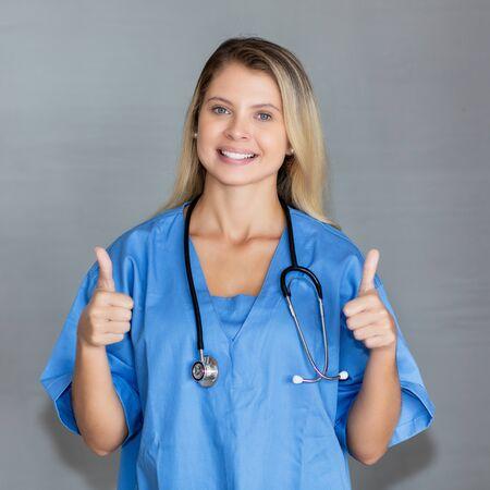 Portrait of beautiful blond nurse showing both thumbs up Stockfoto
