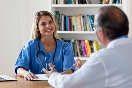 Laughing blond nurse talking with doctor Stock Photo - 131099149