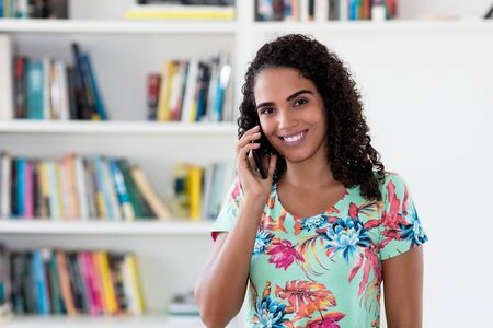 Talking latin american woman with mobile phone