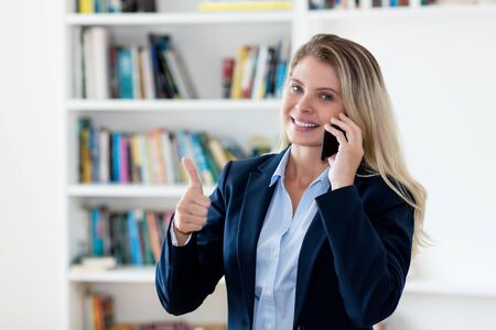 Successful blond businesswoman talking with client at phone