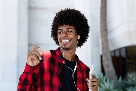 African american hipster young adult with earphones listening music Stockfoto