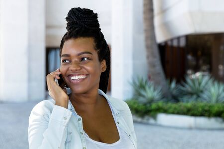 African american young adult woman laughing at phone Stockfoto
