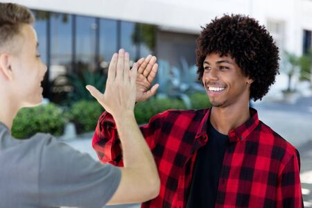 High five of african american man with young adult friend Stockfoto