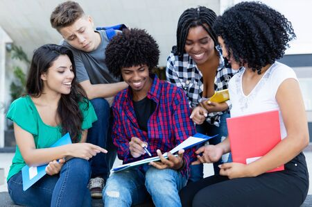 Group of american and latin and african students talking about homework