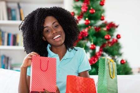 Laughing african american woman with christmas presents