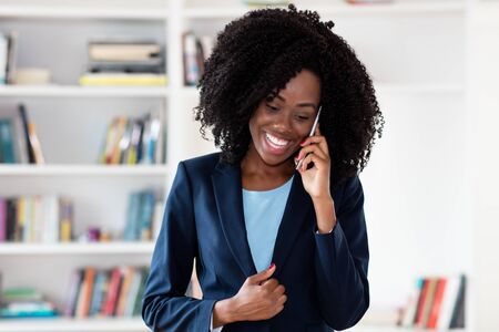 Laughing african american businesswoman with business blazer talking with customer