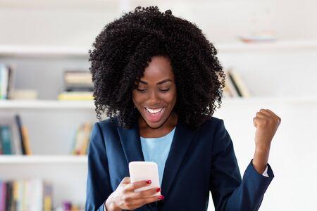 Donna d'affari afroamericana che riceve un messaggio con buone notizie Archivio Fotografico