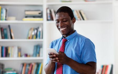 African american businessman sending message with mobile phone Stockfoto