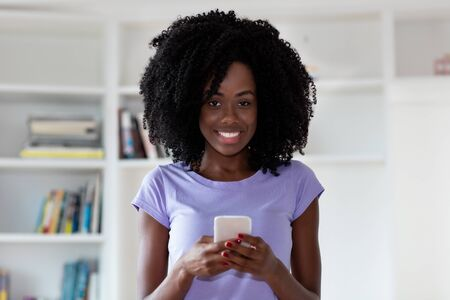 Laughing african american sending message with mobile phone