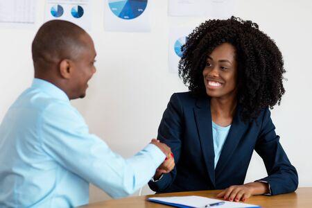 Uścisk dłoni afroamerykańskiej bizneswoman z biznesmenem po rozmowie kwalifikacyjnej