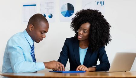 African american businesswoman talking with client about contract