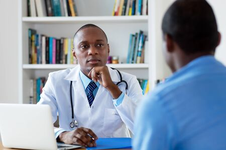 African american doctor listening to problems of male patient