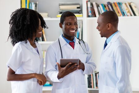 African american doctors and nurse talking about patient Stockfoto