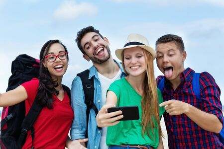 Group of american tourists taking selfie with mobile phone