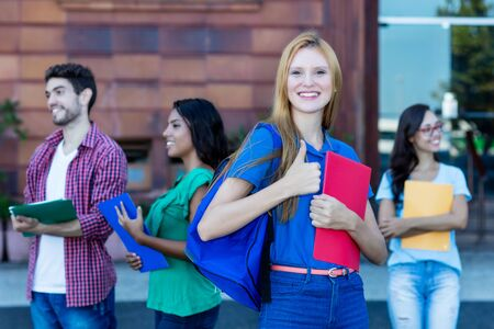 Cheering female student with red hair and group of young adults Banque d'images - 132556919