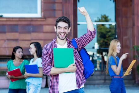 Cheering hipster male student with group of young adults