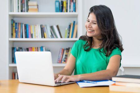 Lachende Latijns-Amerikaanse jonge volwassen vrouw op computer Stockfoto