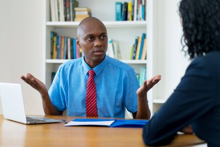 African american businessman talking to lazy employee Stock Photo