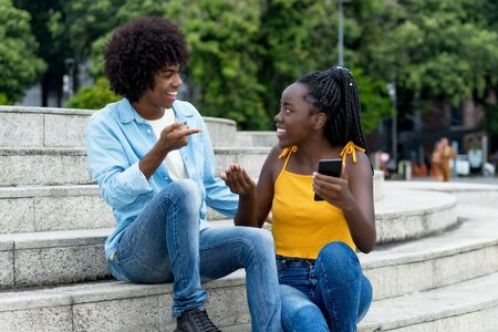 African american young adults with mobile phone in discussion