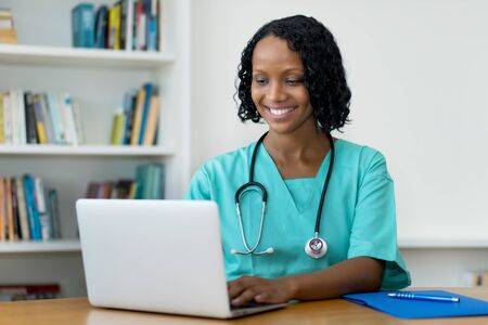 African american female doctor answering questions of patient online