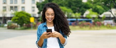 Beautiful brazilian young adult woman with retainer sending message with mobile phone