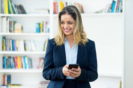 Laughing blond businesswoman with tracing app at mobile phone Stok Fotoğraf