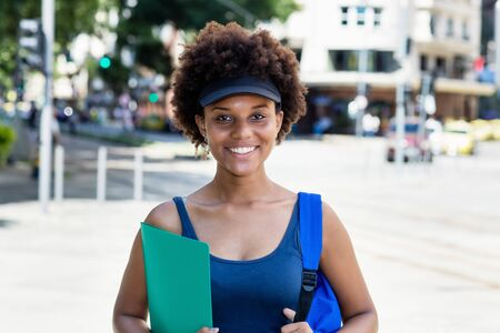 Laughing african american female student outdoor in city