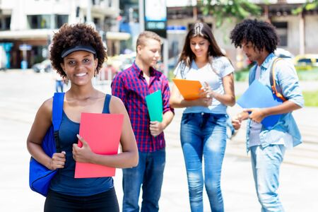 Young afro american female student with group of multi ethnic young adults