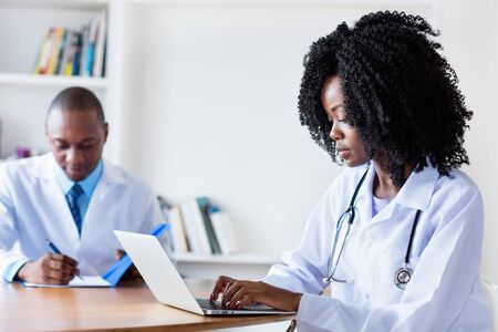 African american medical student at computer with male doctor Imagens