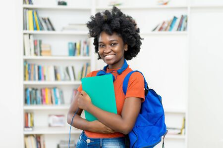 Beautiful afro american female college student with backpack and paperwork