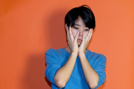 Shocked young adult man with blue shirt Standard-Bild