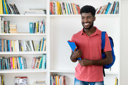 Young afro american male student with backpack and copy space